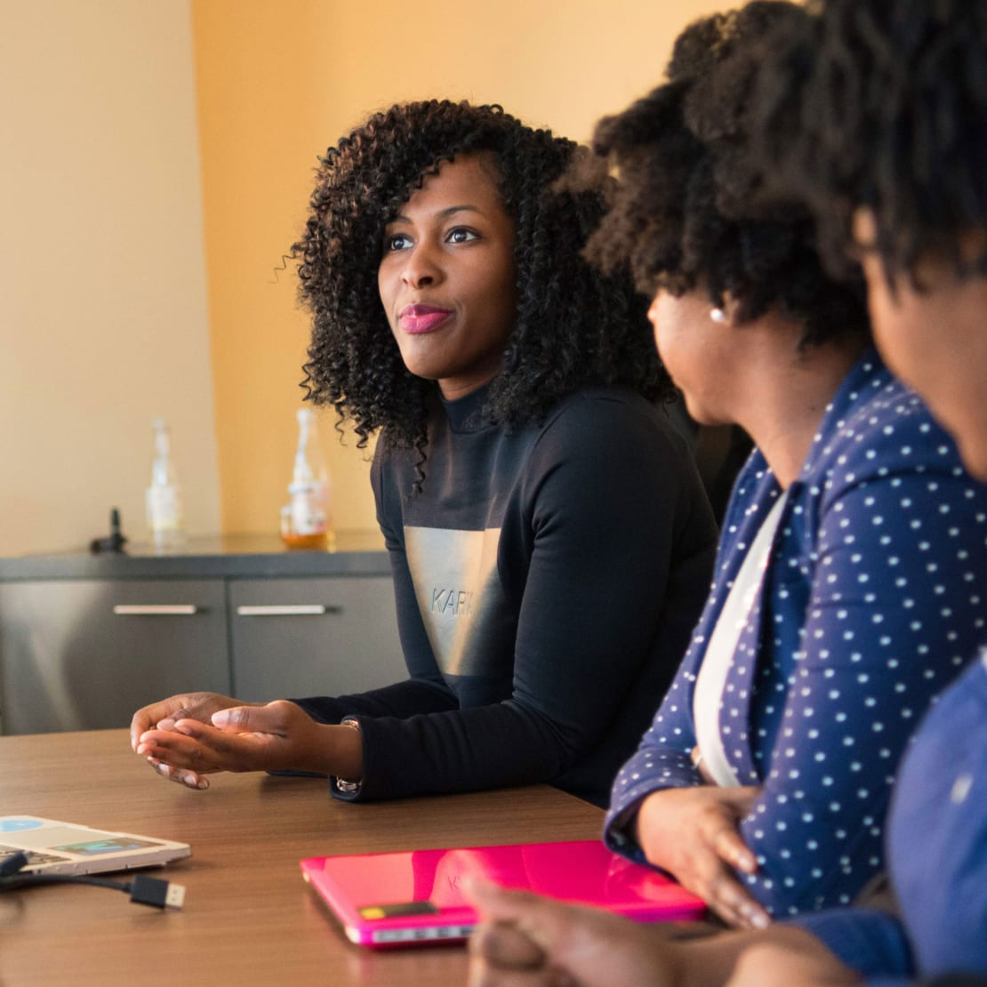Woman sitting with health and social services colleagues at conference table